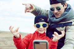 Jonge vader met zijn zoon die pret buiten op de lentegebied hebben, gelukkige familie die, levensstijlmensen die selfie maken gli stock foto's