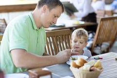 Jonge vader voedende zoon Stock Foto