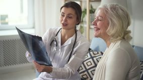 Jonge vakman arts die met oude vrouw over haar R?ntgenstraal spreken stock footage
