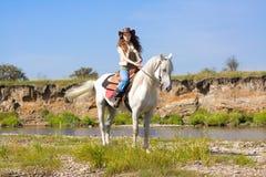 Jonge veedrijfster op wit paard bij de rivier Stock Fotografie
