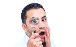 Jonge verbaasde mens die met magnifer kijkt Stock Foto's