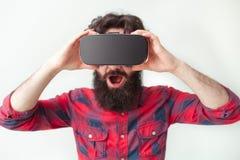 Jonge verbaasde mens die VR-hoofdtelefoon dragen Stock Foto
