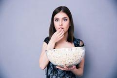Jonge verbaasde vrouw die popcorn eten Stock Foto's