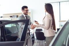 Jonge verkoopster die met cli?nt in het autohandel drijven werken stock foto