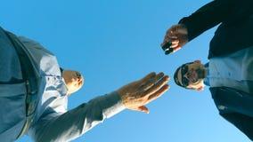 Jonge verkoper in formele kostuumgroet met mannelijke koper en het geven van hem sleutels van auto op de blauwe hemelachtergrond  stock video