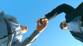 Jonge verkoper in formele kostuumgroet met mannelijke koper en het geven van hem sleutels van auto op de blauwe hemelachtergrond  stock footage