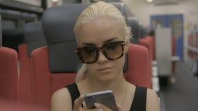 Jonge vermoeide blondevrouw die smartphone in metro gebruiken bij metro stock video