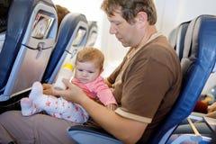 Jonge vermoeide vader en zijn schreeuwende babydochter tijdens vlucht op vliegtuig die op vakanties gaan Royalty-vrije Stock Foto