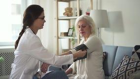 Jonge verpleegster die bloeddruk en bezoek hogere vrouw meten bij h stock videobeelden