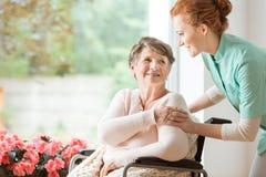 Jonge verpleegster die een bejaarde in een rolstoel helpen Verzorging ho stock afbeelding