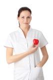 Jonge verpleegster met hart in haar hand Stock Afbeeldingen