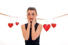 Jonge verraste donkerbruine dame met rood hart in studio glimlachen op camera geïsoleerd op witte achtergrond Rood nam toe Stock Foto