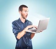 Jonge verraste mens het houden van laptop royalty-vrije stock afbeelding