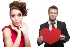 Jonge verraste vrouw en knappe man die rood hart op whit houden Royalty-vrije Stock Afbeeldingen