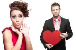 Jonge verraste vrouw en knappe man die rood hart op whit houden Royalty-vrije Stock Afbeelding