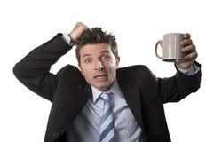 Jonge verslaafden bedrijfsmens in kostuum en band die lege kop van koffie bezorgd houden Stock Fotografie