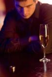 Jonge in verwarring gebrachte mens met ring en champagneglas in restaurant Stock Afbeelding