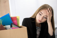 Jonge verworpen vrouwelijke werknemer in bureauzitting dichtbij kartondoos Stock Afbeeldingen