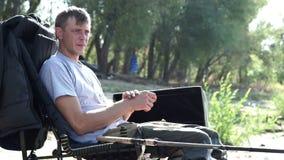 Jonge visserszitting die op stoel door rivier bijna hengel op beet wachten stock videobeelden
