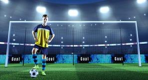 Jonge voetballer met bal voor het doel op een professi stock fotografie