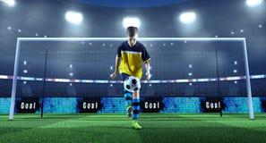 Jonge voetballer met bal voor het doel op een professi stock foto's