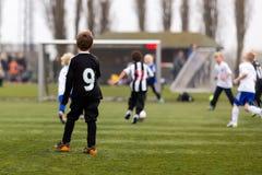 Jonge voetballers tijdens het spel van het jongensvoetbal Stock Foto