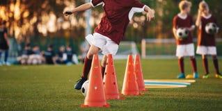 Jonge voetbalsters die op hoogte opleiden De kegelboor van de voetbalslalom royalty-vrije stock fotografie