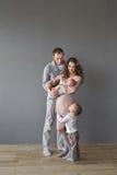 Jonge volwassen familie met een zuigeling en een kind in een studio royalty-vrije stock foto's