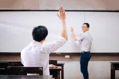 Jonge volwassen mannelijke student die handen omhoog in de lucht opheffen om vragen van een andere mannelijke leraar te stellen royalty-vrije stock afbeelding