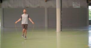 Jonge volwassen mens die het overslaan oefening met touwtjespringen doen tijdens fitness sporttraining Grunge industriële stedeli stock videobeelden