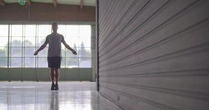 Jonge volwassen mens die het overslaan oefening met touwtjespringen doen tijdens fitness sporttraining Grunge industriële stedeli stock footage