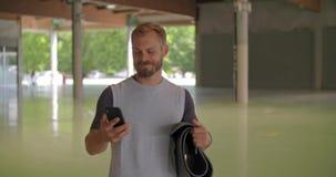 Jonge volwassen mens die met rollende mat lopen die smartphone gebruiken vóór fitness sporttraining Grunge industriële stedelijke stock videobeelden