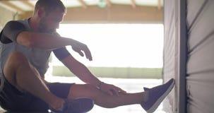 Jonge volwassen mens die oefening zitten-UPS doen tijdens fitness sporttraining Front View Grunge industriële stedelijke opleidin stock videobeelden