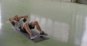 Jonge volwassen mens die oefening zitten-UPS doen tijdens fitness sporttraining Grunge industriële stedelijke opleiding 4k langza stock footage