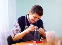 Jonge volwassen mens met handicap belast met vakmanschap op prac Stock Foto