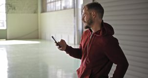 Jonge volwassen mens met sweatshirt die met een kap smartphone gebruiken tijdens fitness sporttraining Grunge industriële stedeli stock video