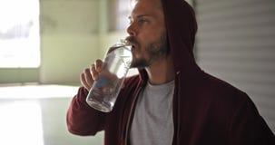 Jonge volwassen mens met sweatshirt drinkwater die met een kap tijdens fitness sporttraining rusten Grunge industriële stedelijk stock videobeelden