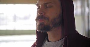 Jonge volwassen mens met sweatshirt drinkwater die met een kap tijdens fitness sporttraining rusten Grunge industriële stedelijk stock video