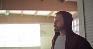 Jonge volwassen mens met sweatshirt drinkwater die met een kap tijdens fitness sporttraining rusten Grunge industriële stedelijk stock footage