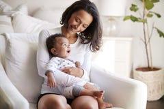 Jonge volwassen moederzitting in een leunstoel in haar slaapkamer, holding haar oude babyzoon van drie maanden in haar wapens en  stock foto