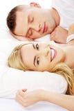 Jonge volwassen paarslaap op het bed Stock Afbeeldingen