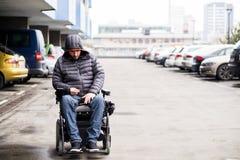 Jonge, volwassen rolstoelgebruiker op een parkeerterrein met exemplaarruimte stock foto