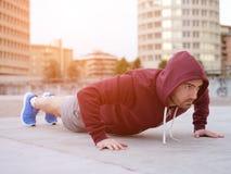 Jonge volwassen sportman die in de stad uitwerken Stock Foto's