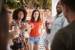 Jonge volwassen vrienden die zich met dranken bij een binnenplaatspartij bevinden royalty-vrije stock foto