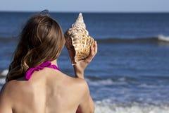 Jonge volwassen vrouw die een triton-zeeschelp houden Stock Fotografie