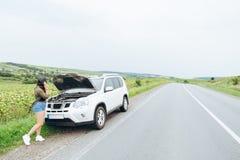 Jonge volwassen vrouw die zich dichtbij gebroken auto op weg bevinden en talkin stock fotografie