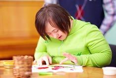 Jonge volwassen vrouw met handicap belast met vakmanschap in revalidatiecentrum Stock Afbeelding