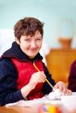 Jonge volwassen vrouw met handicap belast met vakmanschap in revalidatiecentrum Stock Foto's