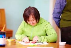 Jonge volwassen vrouw met handicap belast met vakmanschap in revalidatiecentrum royalty-vrije stock foto
