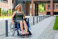 Jonge volwassen vrouw op rolstoel op de straat Stock Afbeelding